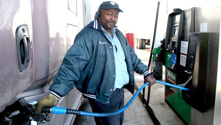truck driver pumping diesel gas in semi