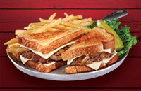 juicy steak burger patty melt topped with melted Swiss cheese and grilled onions on grilled rye with fries and a pickle on a skillet