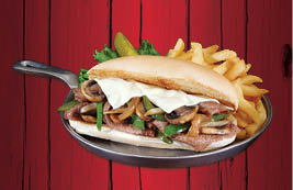 Philly Cheesesteak sandwich with Thinly-sliced beef piled high on a bun with grilled onions, mushrooms, bell peppers, Swiss cheese and a side of fries