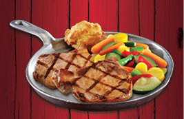 Two juicy bone-in, center-cut chops seasoned with fries and vegetables