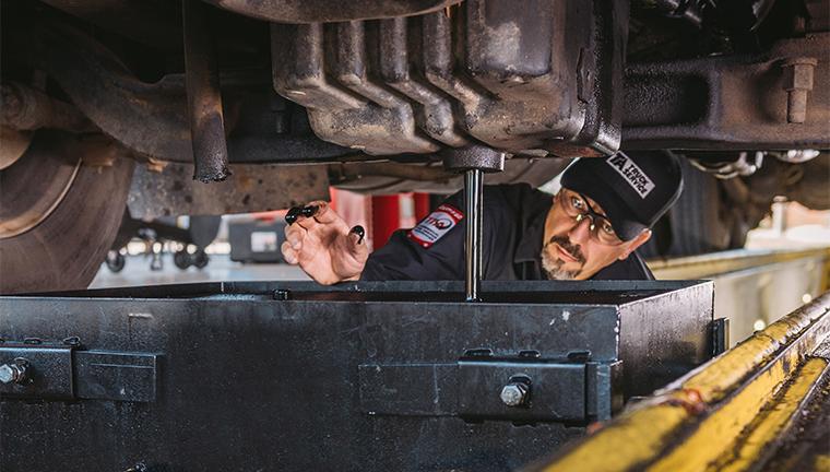 ta truck service technician completing oil change service