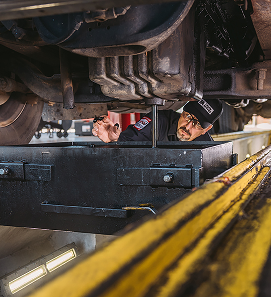 Service technician checking oil level