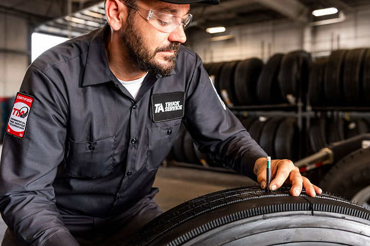 Technician inspecting commercial truck tires