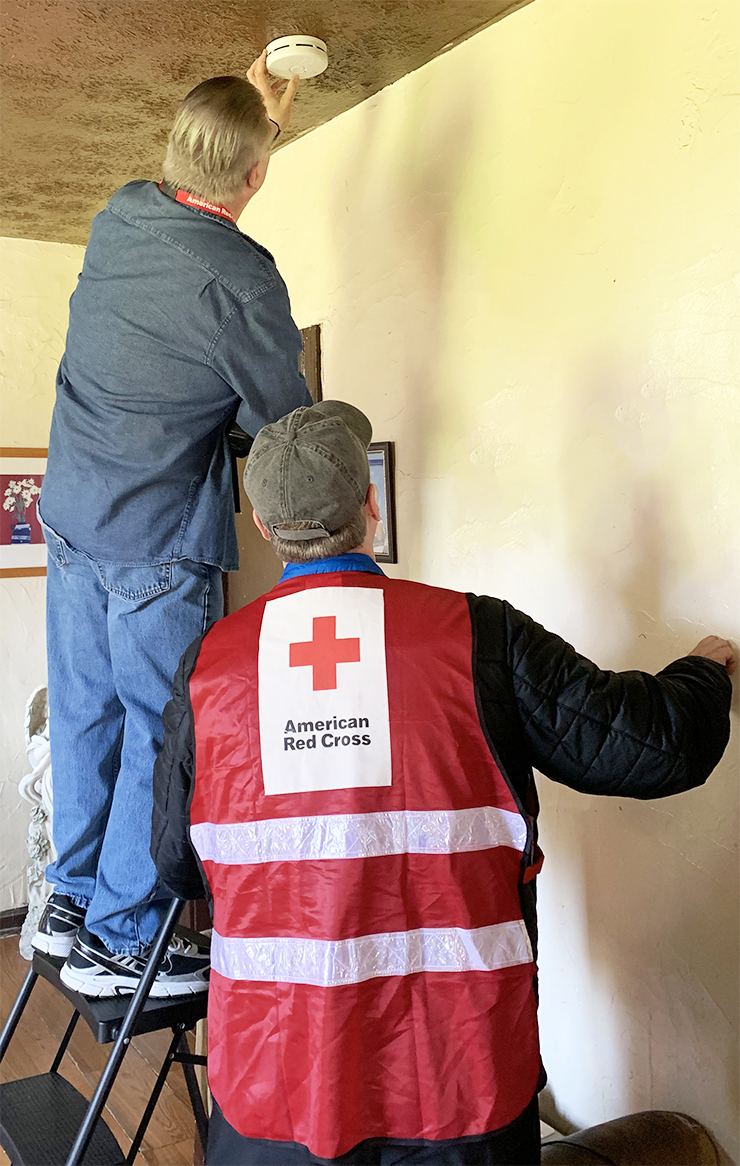 Volunteer installing a new smoke alarm