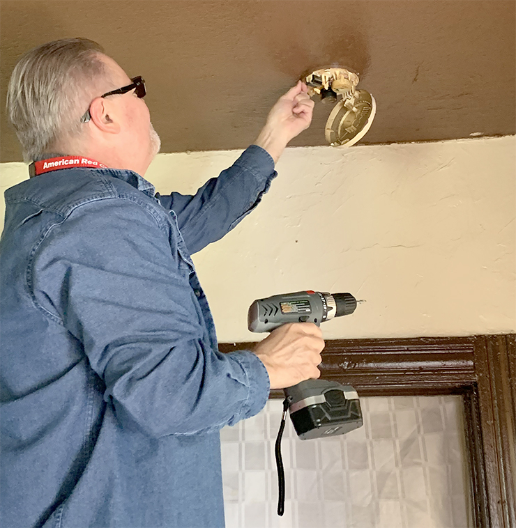 Volunteer removing old smoke alarm