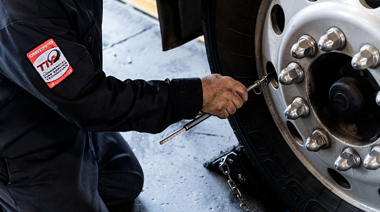 Technician checking commercial tire air pressure.